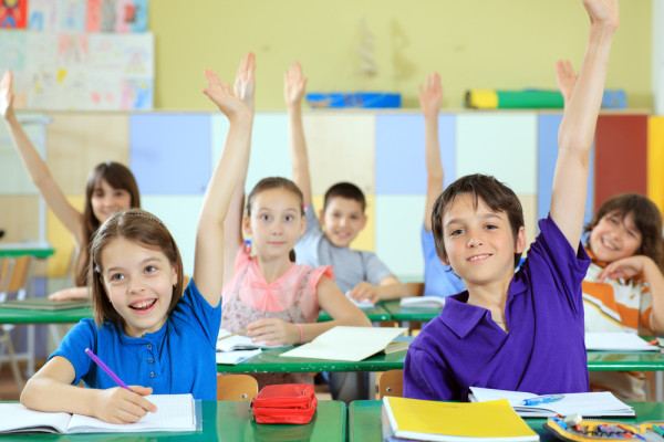 Elementary-school-students-raising-hands-in-classroom_
