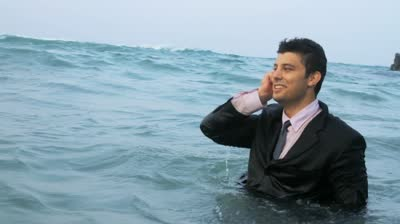 stock-footage-business-man-calling-cell-phone-in-the-sea-hd