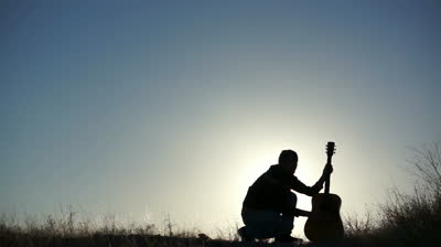stock-footage-silhouette-of-a-performance-artist-twirling-his-guitar-while-it-s-set-on-the-ground
